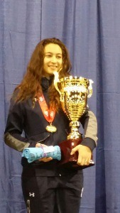 young woman holds gigantic gold trophy and other gifts
